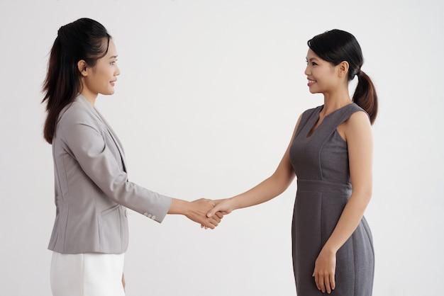 Две азиатские деловые женщины стоят в помещении, пожимают друг другу руки и улыбаются