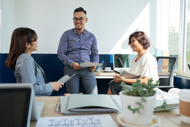 Трое коллег обсуждают проект на приеме в офисе
