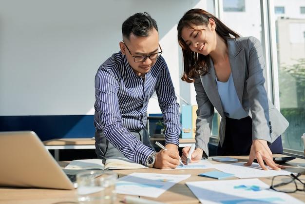 Два коллеги работают над документацией вместе стоя в освещенном солнцем офисе