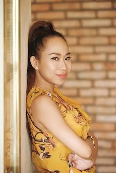 胸の下に折り畳まれた壁の腕に背を向けて立っているアジアの女性の側面図