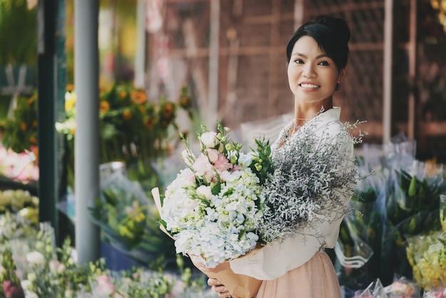 Хорошо одетая азиатская леди позирует возле цветочного магазина с большим сложным букетом