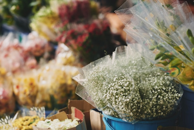 Букеты разных цветов, выставленные в ведрах у цветочного магазина