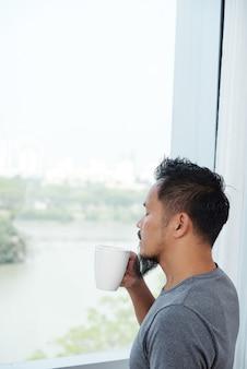 アジア人の男性が窓の前に立って、目を閉じて一杯のコーヒーの臭いがします。