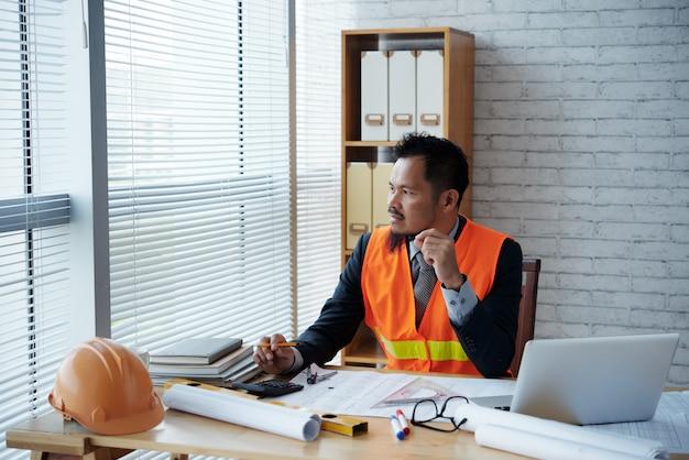 Азиатский руководитель строительной фирмы в деловом костюме и жилет безопасности, сидя в офисе