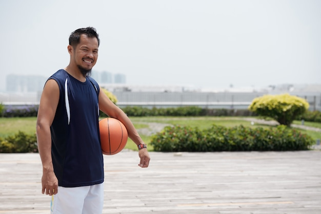Азиатский человек, стоящий на открытом воздухе на стадионе, держа баскетбол и улыбается
