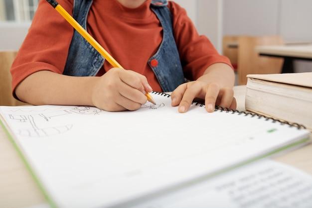 Неузнаваемый ребенок, сидящий за столом и рисующий в тетради с карандашом