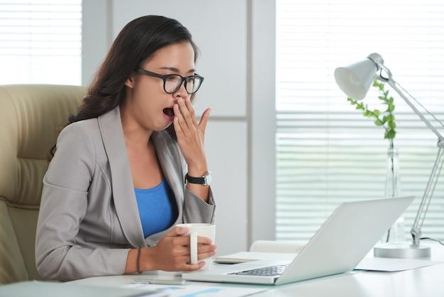 Азиатская женщина сидит за столом в офисе, глядя на экран ноутбука и зевая