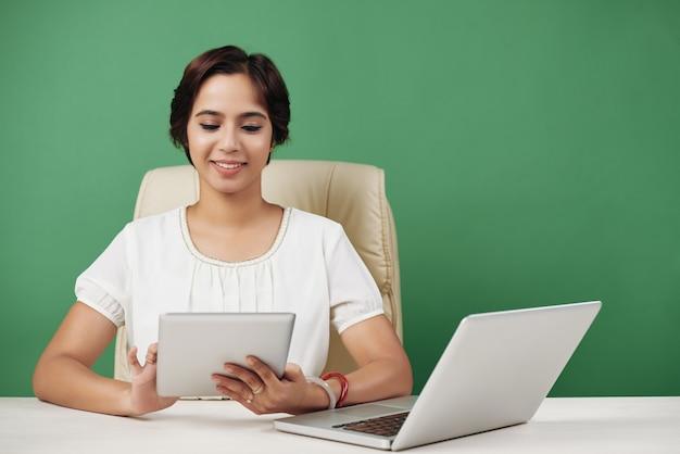 手でタブレットを持つ若いビジネス女性