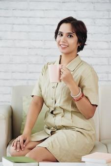 お茶の大きなマグカップを楽しむ女性
