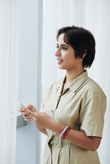 スマートフォンでオフィスの窓に立っていると外を見てビジネスドレスの混血女性