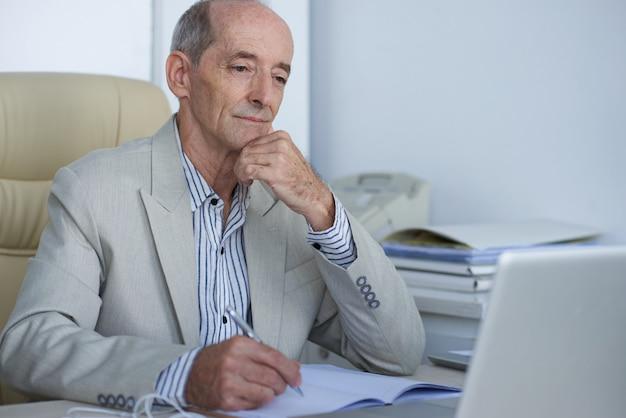 Пожилой руководитель бизнеса работая в офисе