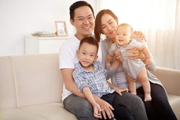 Любящая азиатская пара позирует на диване у себя дома с маленьким сыном и ребенком