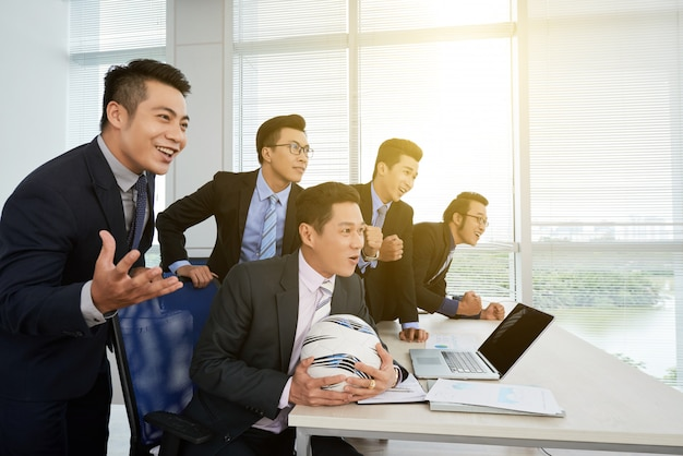 サッカーの試合を見ているアジア系のビジネスマン