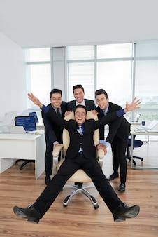 Радостные менеджеры позируют для фотографии