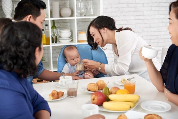 朝食のテーブルで大きなアジアの家族