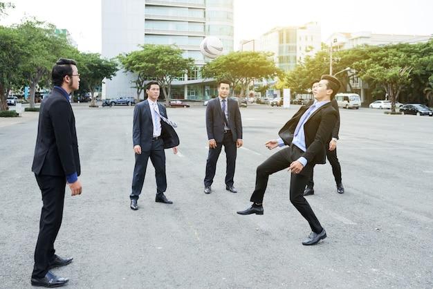 同僚とサッカーをする