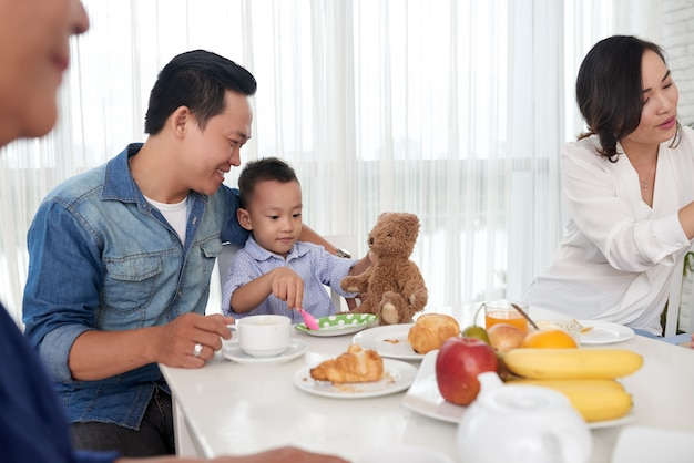 Отец и сын на завтраке с семьей