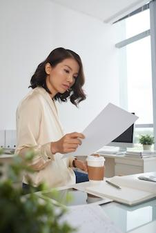 Серьезная женщина читает договор