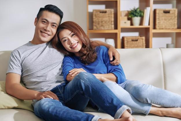 Красивая азиатская пара отдыхает вместе на диване у себя дома и улыбается