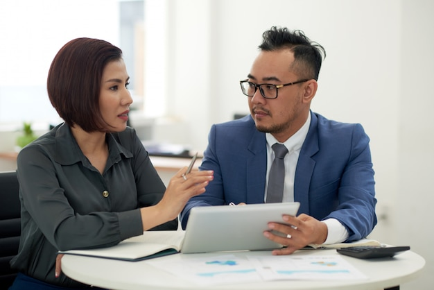 アジアの男性と女性のタブレットで屋内で座っていると話しているビジネス装いで