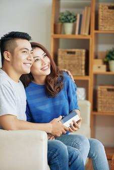 幸せなアジアカップルが一緒に自宅でソファに座って、ハグとよそ見