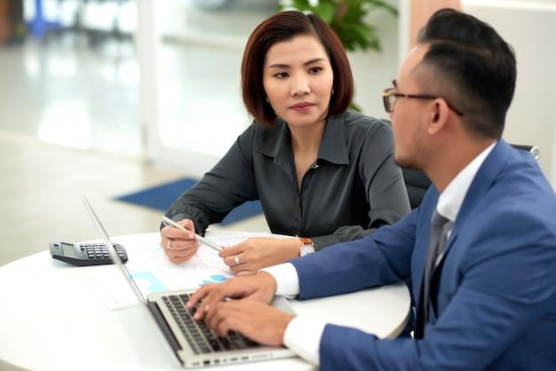 アジアの男性と女性のビジネスの服装の室内のテーブルに座っていると話して