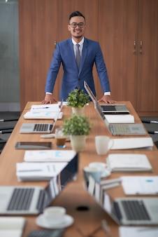 企業の会議室での長い会議テーブルの上に立っているアジア系のビジネスマン