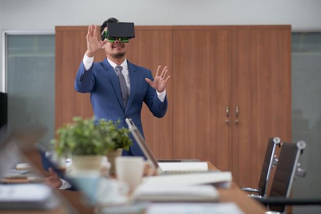 Азиатский генеральный директор в костюме, используя гарнитуру виртуальной реальности в зале заседаний