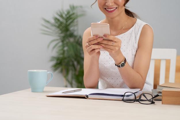 職場のテーブルに座って、スマートフォンを使用して認識できないエレガントな女性