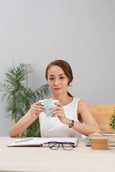 Молодая азиатская женщина сидя на таблице внутри помещения и держа кружку