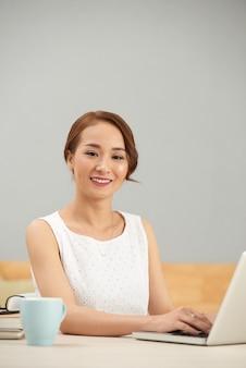Улыбаясь азиатская женщина сидит за столом в помещении и с помощью ноутбука