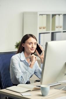 コンピューター画面の前のオフィスに座っていると電話で話している若い白人女性