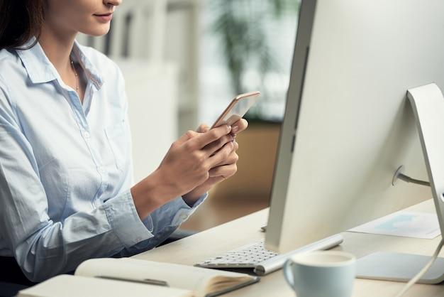 До неузнаваемости женщина сидит в офисе перед компьютером и с помощью смартфона