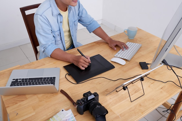 Неузнаваемый фотограф сидит за столом и ретуширует фотографии на компьютере
