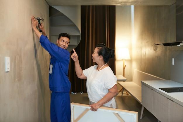 釘を打つ陽気なアジアの便利屋と指示を与える女性の住宅所有者
