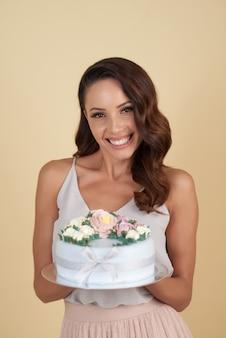 精巧なバースデーケーキとスタジオでポーズ美しい若い白人女性