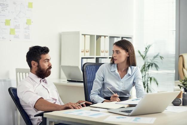 Средний снимок двух коллег, обсуждающих бизнес в офисе