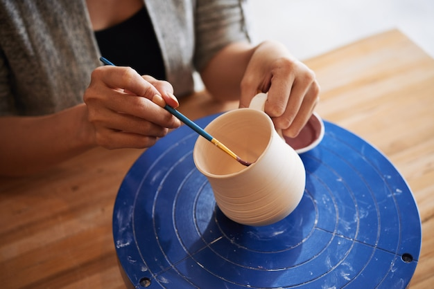 手作りの粘土のマグカップを飾る女性の手のクローズアップ
