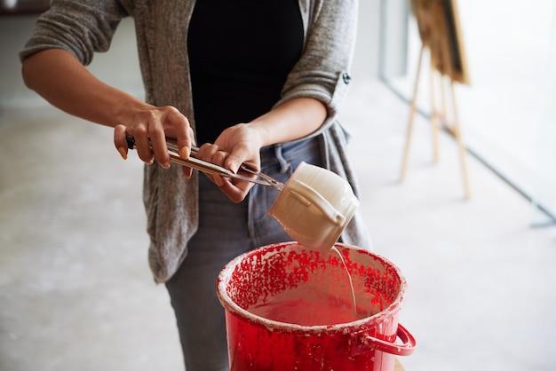 手作りマグカップを艶出しする認識できない女性陶工のクローズアップ
