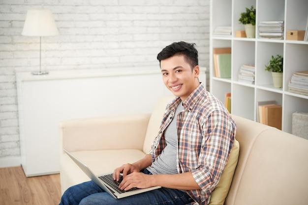 アジア人の男性が自宅のソファでラップトップ上のフリーランスの仕事をしています