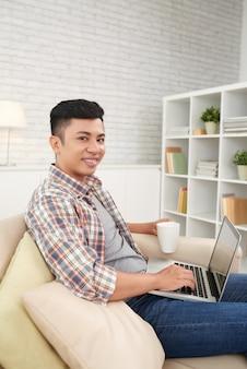 Молодой фрилансер работает на ноутбуке, сидя на диване у себя дома, глядя на камеру