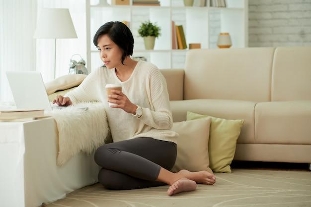家の快適さを楽しんでいる若いアジア女性