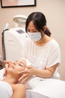 白人のクライアントの顔のマッサージを与えるアジアのメークアップアーティスト