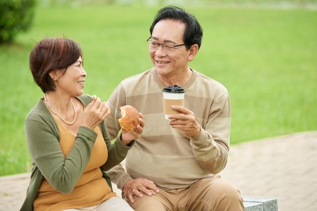 成熟した男と公園でデートを持つ愛の女