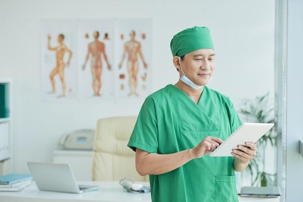 アジアの医師の身に着けている緑の制服を着た水平上半身の肖像画
