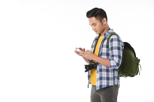 スマートフォンを使用してバックパックで若いアジア観光客の側面図