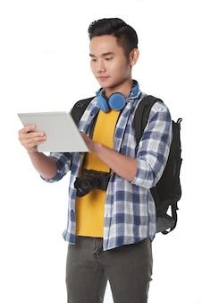 Средний снимок молодого человека с рюкзаком с помощью планшетного пк