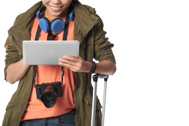 Середине секции улыбается женщина турист, глядя на экран планшетного пк