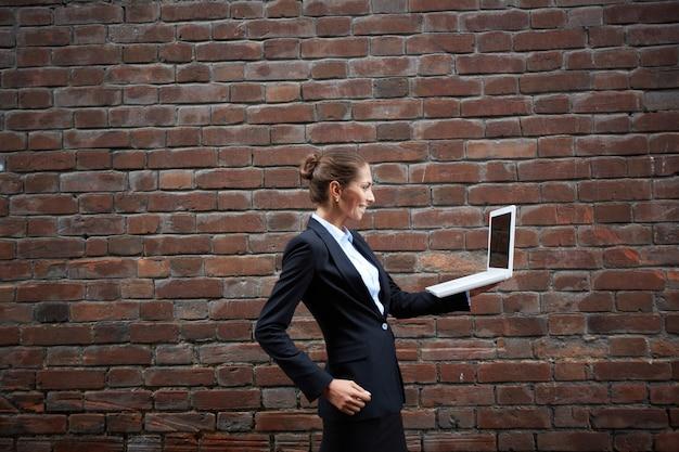 ノートパソコンを持って歩く女性