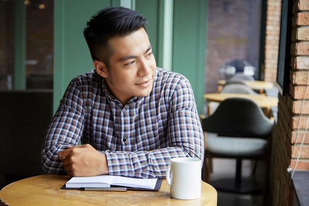 Крупным планом вдумчивый человек, глядя на окна в кафе